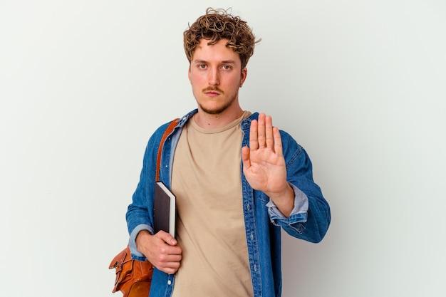 Jonge studentenmens die op witte muur wordt geïsoleerd die zich met uitgestrekte hand bevindt die stopbord toont, dat u verhindert.