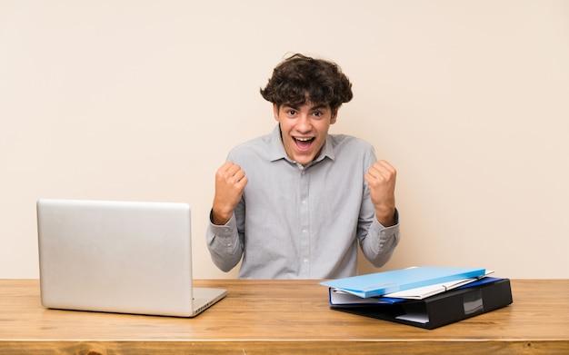 Jonge studentenmens met laptop die een overwinning in winnaarpositie viert
