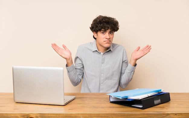 Jonge studentenmens met laptop die twijfelsgebaar maken