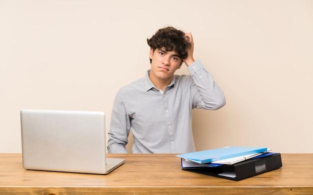 Jonge studentenmens met laptop met een uitdrukking van frustratie en niet begrip