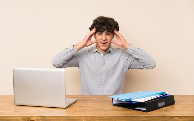 Jonge studentenmens met laptop met verrassingsuitdrukking