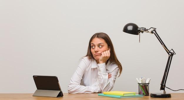 Jonge studentenvrouw die aan haar bureau het denken aan iets werken, die aan de kant kijken