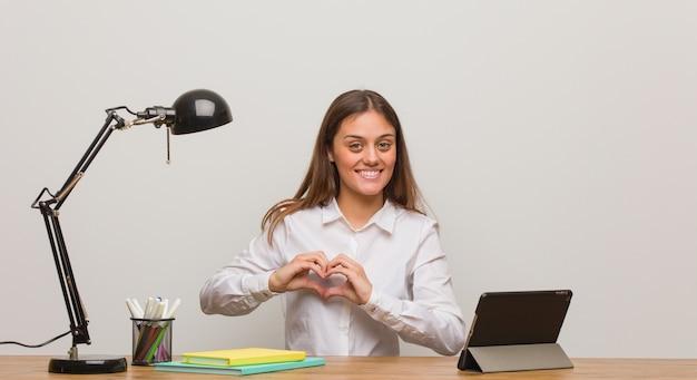 Jonge studentenvrouw die aan haar bureau werkt dat een hartvorm met handen doet