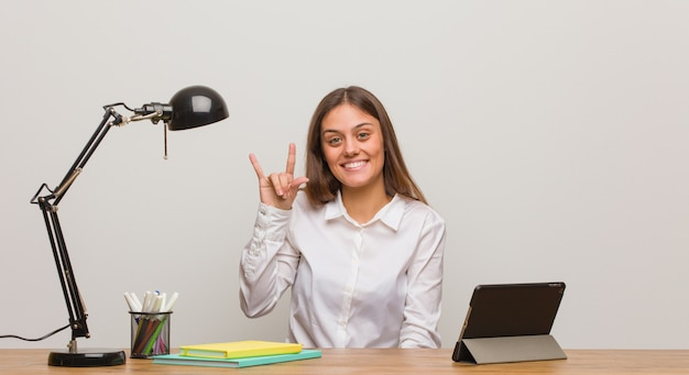 Jonge studentenvrouw die aan haar bureau werkt dat een rotsgebaar doet