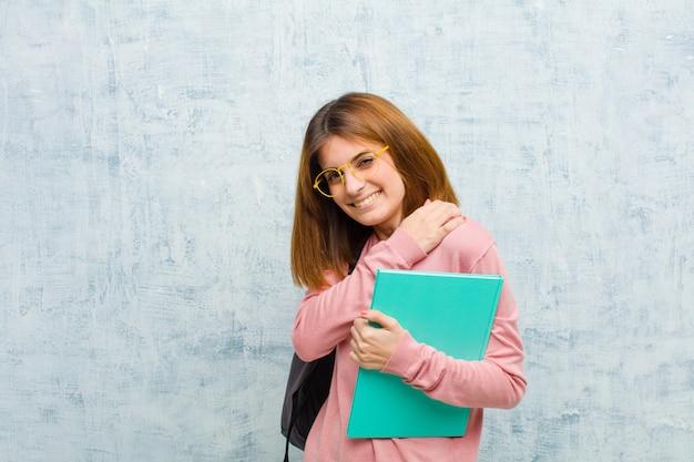 Jonge studentenvrouw die angstig, ziek, ziek en ongelukkig voelen, die aan een pijnlijke maagpijn of griep lijden tegen de achtergrond van de grungemuur