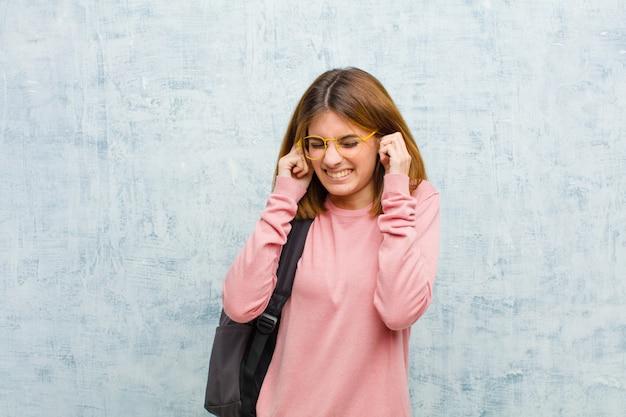 Jonge studentenvrouw die boos, gestrest en geërgerd kijkt, beide oren bedekkend met een oorverdovend geluid, geluid of luide muziek