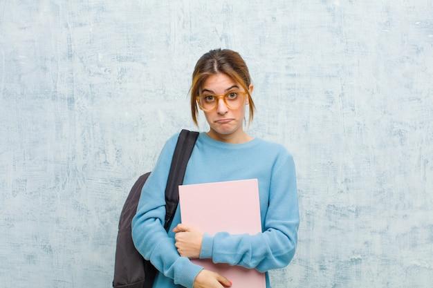Jonge studentenvrouw die droevig en gestresst, verstoord wegens een slechte verrassing, met een negatieve, bezorgde blik tegen de achtergrond van de grungemuur voelt