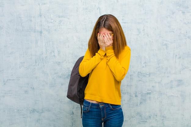 Jonge studentenvrouw die droevig, gefrustreerd, zenuwachtig en depressief voelen, die gezicht behandelen met beide handen, huilend tegen grungemuur
