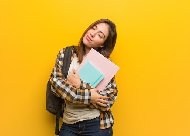 Jonge studentenvrouw die een omhelzing geeft