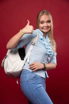 Jonge studentenvrouw die een rugzak draagt, ziet er positief en leuk uit.