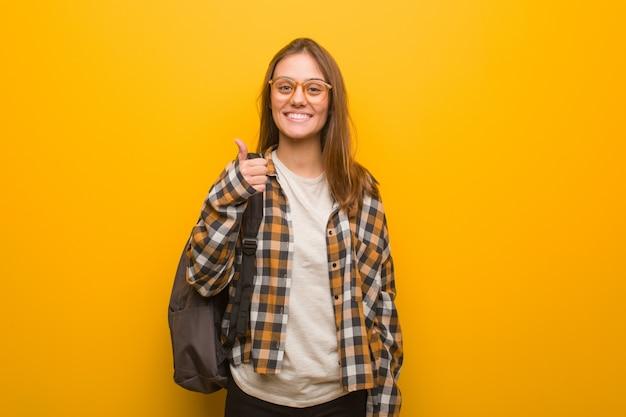 Jonge studentenvrouw die en duim omhoog glimlachen opheffen