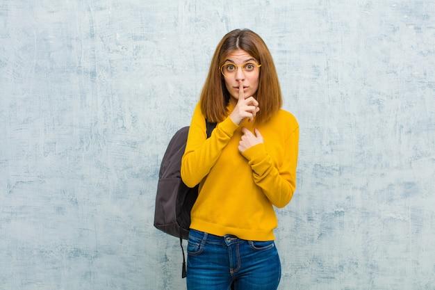 Jonge studentenvrouw die ernstig en kruis met vinger kijkt die aan lippen wordt gedrukt die stilte eisen of stil, die een geheim houden