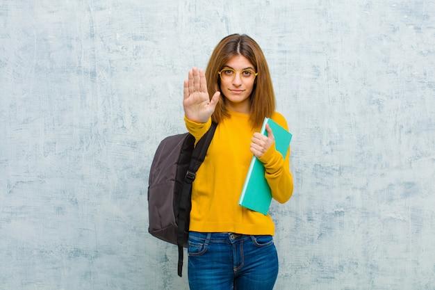Jonge studentenvrouw die ernstig, streng, ontstemd en boos tonend open palm kijken die einde maken gebaar grunge muur