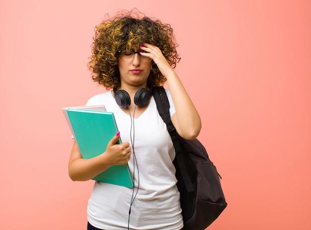 Jonge studentenvrouw die geconcentreerd, nadenkend en geïnspireerd kijkt, brainstormend en verbeeldend met de handen op het voorhoofd op een roze muur