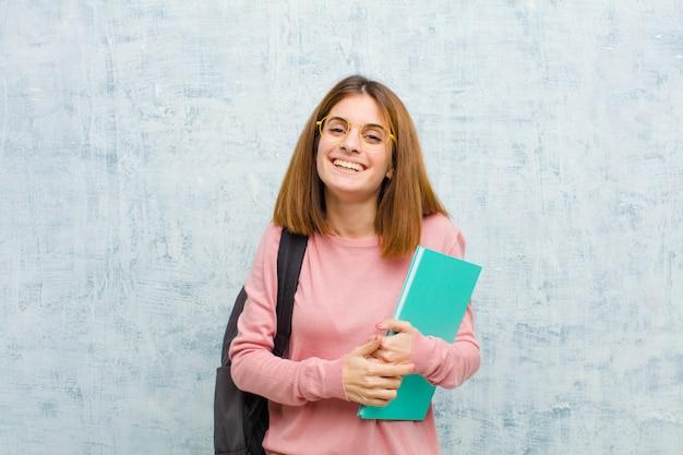 Jonge studentenvrouw die gelukkig en mal met een brede, leuke, gekke glimlach en ogen wijd open tegen grungemuur kijkt