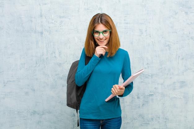 Jonge studentenvrouw die gelukkig en met hand op kin glimlachen kijken, of een vraag benieuwd zijn stellen, die opties grunge muur vergelijken