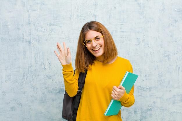 Jonge studentenvrouw die gelukkig en opgewekt glimlachen, golvende hand, u welkom heten en begroeten, of vaarwel zeggen tegen grungemuur