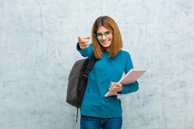 Jonge studentenvrouw die gelukkig en zeker voelen, aan camera met beide handen richten en lachen, die u kiezen tegen grungemuur