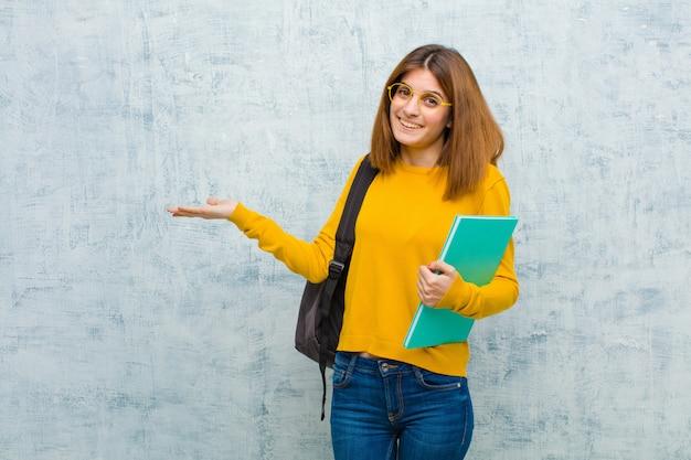 Jonge studentenvrouw die gelukkig onbezorgd en tevreden het glimlachen glimlachen die aan concept of idee op exemplaarruimte aan de kant richten