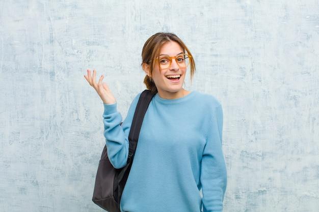 Jonge studentenvrouw die gelukkig, verrast en vrolijk voelen, glimlachend met positieve houding, realiserend een oplossing of een idee