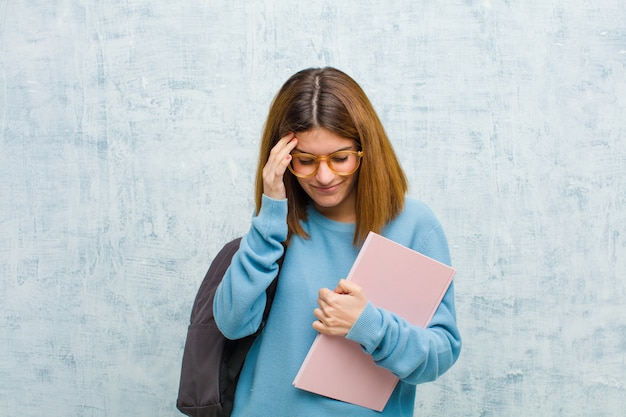 Jonge studentenvrouw die gestrest en gefrustreerd kijkt, werkt onder druk met hoofdpijn en verontrust met problemen
