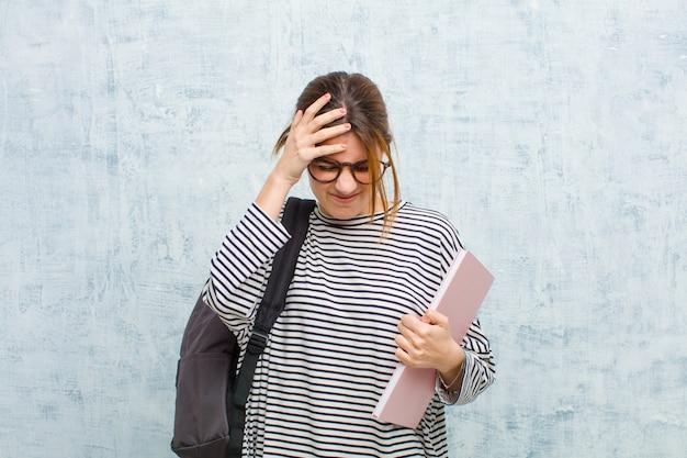 Jonge studentenvrouw die gestrest en gefrustreerd voelen, handen opheffen, moe, ongelukkig en met migraine tegen de muur van de grungemuur voelen