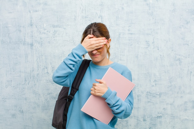 Jonge studentenvrouw die gezicht behandelt met beide handen die nee zeggen tegen de camera! afbeeldingen weigeren of foto's verbieden tegen een grunge muur