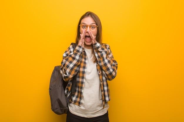 Jonge studentenvrouw die iets blij naar voren schreeuwt