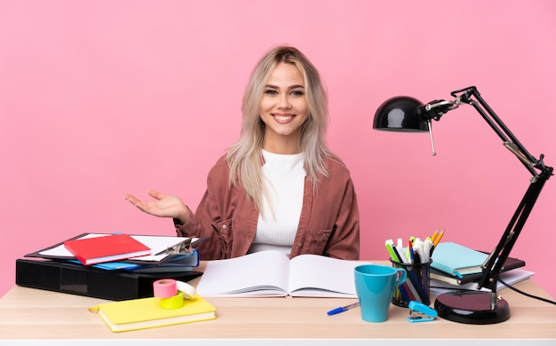 Jonge studentenvrouw die in een lege ruimte van de lijstholding denkbeeldig aan de palm werkt
