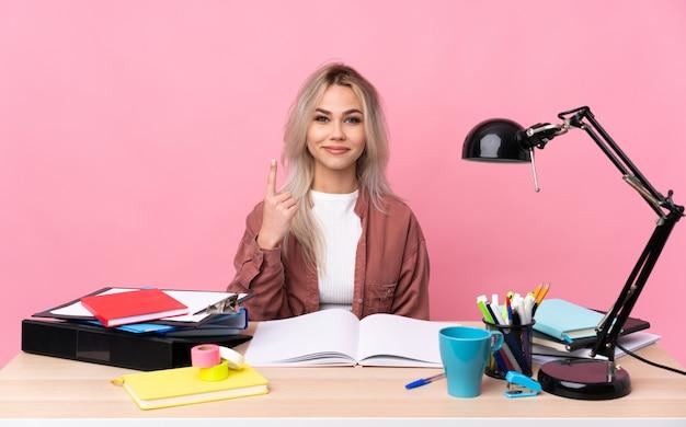 Jonge studentenvrouw die in een lijst werkt die met de wijsvinger een groot idee richt