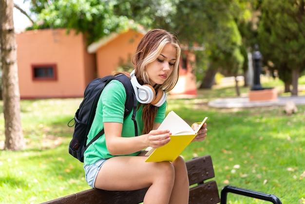 Jonge studentenvrouw die in openlucht een notitieboekje houdt