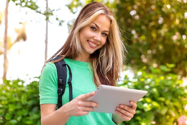 Jonge studentenvrouw die in openlucht een tablet houdt