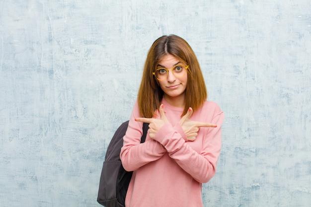 Jonge studentenvrouw die in verwarring gebracht en verward, onzeker en in tegenovergestelde richtingen met twijfels op grungemuur kijken