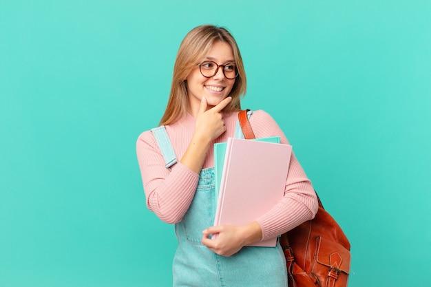 Jonge studentenvrouw die lacht met een gelukkige, zelfverzekerde uitdrukking met de hand op de kin