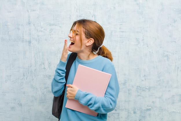 Jonge studentenvrouw die lui vroeg in de ochtend geeuwt, en slaperige, vermoeide en verveelde grunge muur kijkt