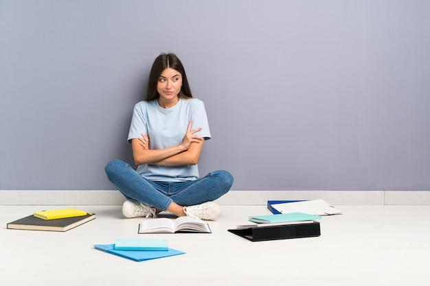 Jonge studentenvrouw die met vele boeken op de vloer een idee denkt