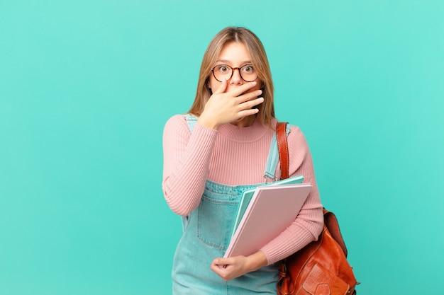 Jonge studentenvrouw die mond bedekt met handen met een geschokte