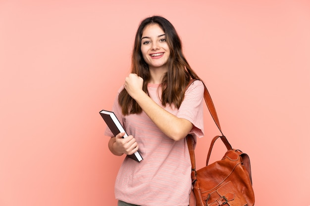 Jonge studentenvrouw die naar de universiteit over geïsoleerde roze muur met verrassingsgelaatsuitdrukking gaat