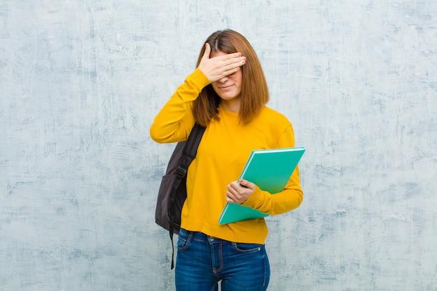 Jonge studentenvrouw die ogen behandelen met één doen doen schrikken of bezorgd gevoel, benieuwd of blindelings wachtend op een verrassing tegen de achtergrond van de grungemuur