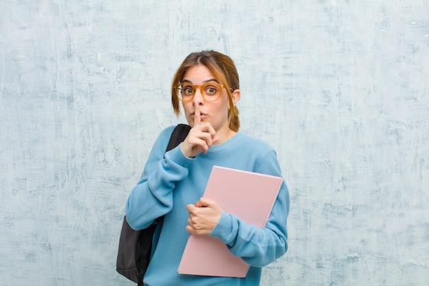 Jonge studentenvrouw die om stilte en stil vraagt, gebaren met vinger voor mond, zeggend shhkeeping een geheime grungemuur