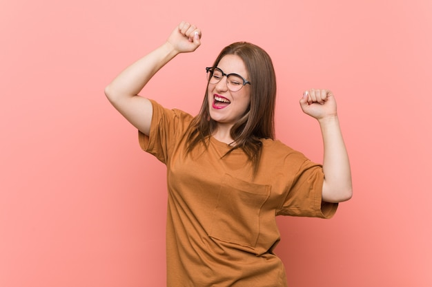 Jonge studentenvrouw die oogglazen draagt die een speciale dag vieren, sprongen en wapens met energie opheffen.