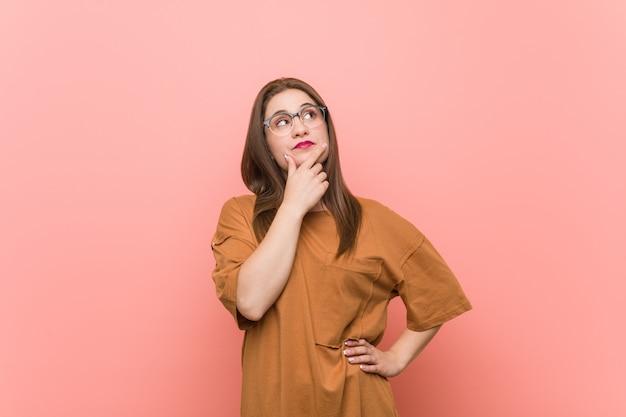 Jonge studentenvrouw die oogglazen draagt die zijdelings met twijfelachtige en sceptische uitdrukking kijken.