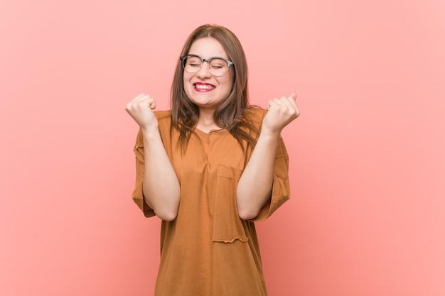 Jonge studentenvrouw die oogglazen dragen die vuist opheffen, gelukkig en succesvol voelen
