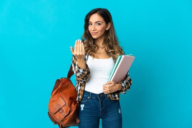 Jonge studentenvrouw die op blauwe muur wordt geïsoleerd die uitnodigt om met hand te komen. blij dat je gekomen bent