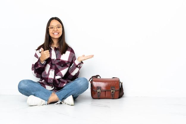 Jonge studentenvrouw die op de vloer zit die copyspace denkbeeldig op de handpalm houdt om een advertentie in te voegen en met omhoog duimen