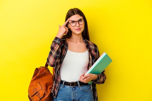 Jonge studentenvrouw die op gele muur wordt geïsoleerd die tempel met vinger richt, denkt, concentreerde zich op een taak.