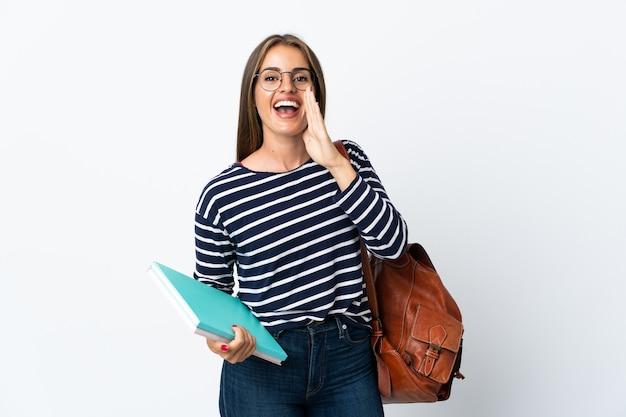 Jonge studentenvrouw die op witte muur wordt geïsoleerd die met wijd open mond schreeuwt