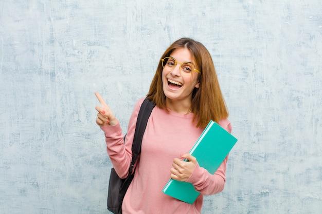 Jonge studentenvrouw die opgewekt en verrast kijkend aan de kant en omhoog kijken om ruimte te kopiëren