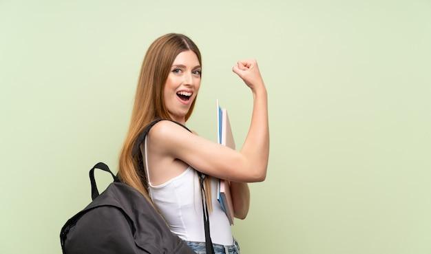 Jonge studentenvrouw die over geïsoleerde groene muur sterk gebaar maken