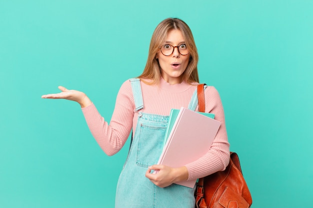 Jonge studentenvrouw die verrast en geschokt kijkt, met open mond terwijl ze een voorwerp vasthoudt